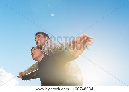 Homosexual couple giving piggyback ride smiling outside. copyspace