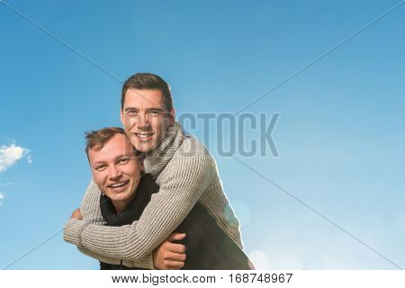 Two young men smiling and holding one another . copyspace
