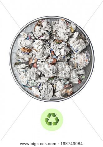Crumpled papers in garbage bin with recycling sign over white background