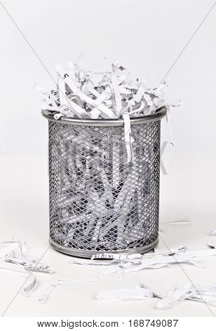 Wastepaper basket with papers lying around over white background