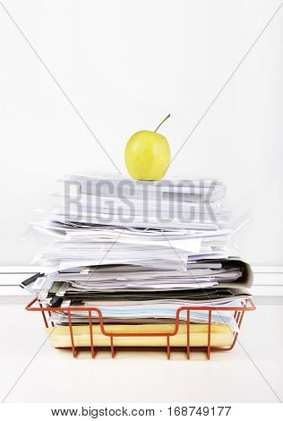 Granny smith apple on stack of documents in desk tray against white wall