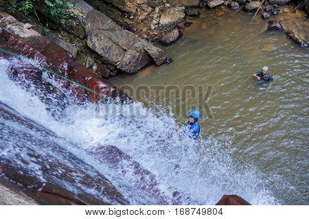 Beaufort,Sabah,Malaysia-Jan 28,2017:Group of adventurer rappelling in Jempangah waterfall at Beaufort,Sabah,Borneo.Waterfall Abseiling activity adventure getting famous in Sabah,Borneo,Malaysia
