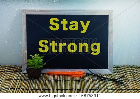 Business & creative concept,Stay Strong word on blackboard with green plant,pen & spectacle eyeglasses.