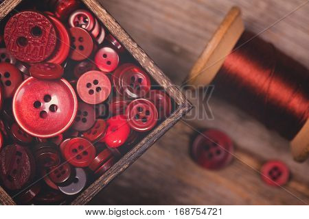 A close up of a box of red buttons, with a spool of red thread alongside. Filtered to have a faded matte finish and nostalgic style.