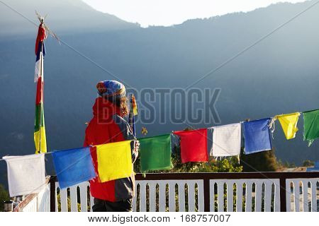 Unrecognizable Tourist In Red Vest Standing At White Fence Of Base Camp Or Village, Looking At Beaut