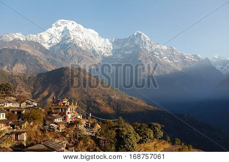 Scenic View Of Houses Of Small Nepali Village Surrounded With Green Slopes And Gigantic Cliffs Of Th