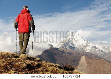 Unrecognizable Hiker Standing On Top Of Mountain With His Back To Camera, Holding Trekking Poles And