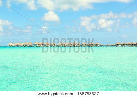 Stunning view of blue turquoise lagoon and far bungalows on background of Bora Bora island French Polynesia