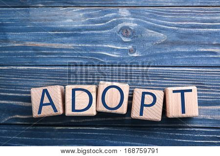 Cubes with word ADOPT on color wooden background