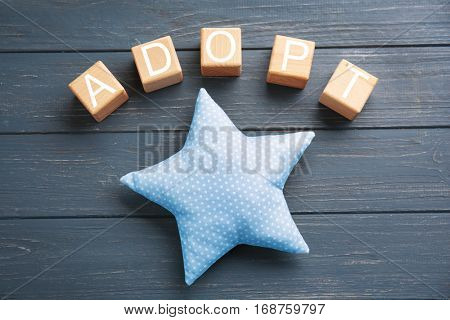 Cubes with word ADOPT and rag star on wooden background
