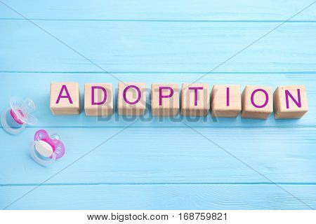 Cubes with word ADOPTION and passifiers on color wooden background