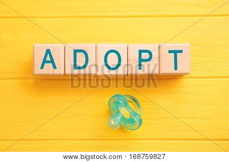 Cubes with word ADOPT and passifier on color wooden background