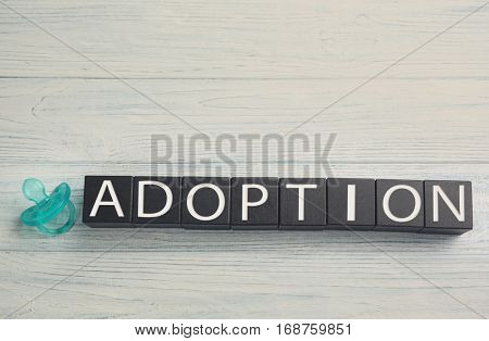 Black cubes with word ADOPTION and passifier on light wooden background