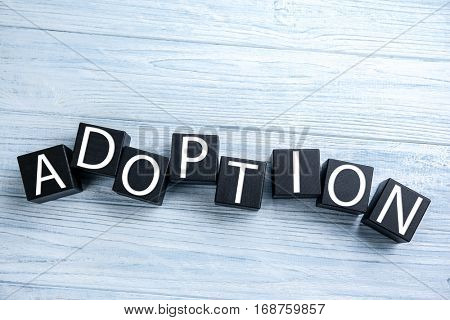 Black cubes with word ADOPTION on light wooden background