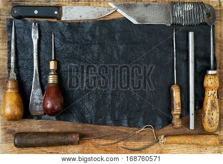 Leather craft tools on a wooden background. Craftmans work desk . Piece of hide and working handmade tools on a work table. Top view.