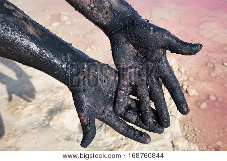 Hands of men smeared black mud. Close-up. At lake Las Salinas, Torrevieja. Spain