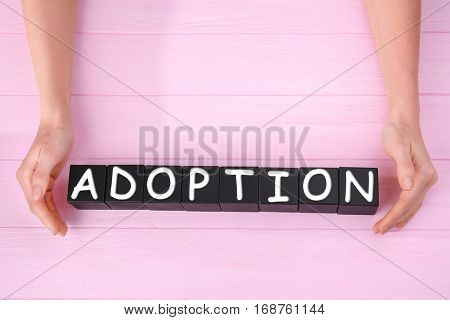 Female hands and black cubes with word ADOPTION on wooden background