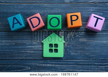 Cubes with word ADOPT and figure in shape of house on color wooden background