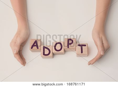 Female hands and wooden cubes with word ADOPT on white background