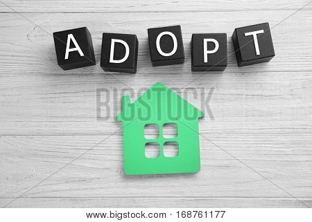 Black cubes with word ADOPT and figure in shape of house on light wooden background