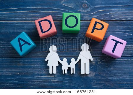 Cubes with word ADOPT and figure in shape of family on color wooden background