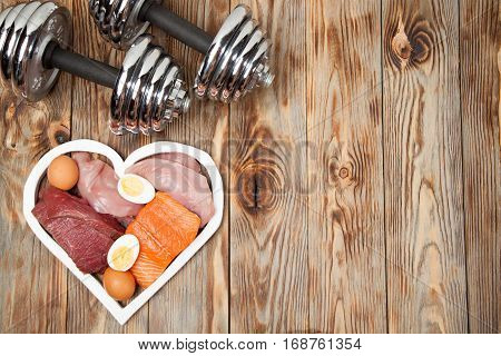 Proteins and dumbbells. Fish cheese eggs meat chicken and heart on wooden background