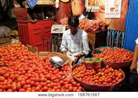 KOLKATA, INDIA - FEBRUARY 11: Indian vendor sits behind a large pile of tomatoes  in New Market in Kolkata on February 11, 2016.