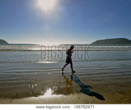 An unidentified silhouetted runner jogs along the sandy beach next to the ocean.