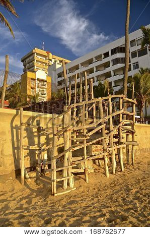 Weathered steps and stairways made of weathered wood poles lead from a sandy resort beach over a retaining wall
