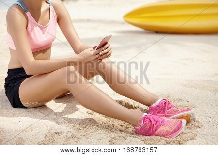 Young Athletic Girl In Pink Sneakers Relaxing On Sand, Using Internet On Her Gadget. Sportswoman Tex