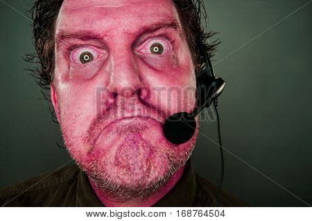 Grumpy Red Eyes and Face Frowning Customer Support Man with Headset.