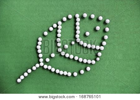 Close-up of push pins forming leaf over green background depicting environmentalism