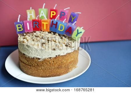 Close-up of birthday candles on torte cake over colored background