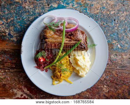Grilled pork ribs with sauerkraut and mash potatoes on grunge peeled paint surface - hearty dish