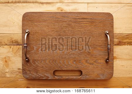 Clean new wooden serving board with metal handles on table shot from above