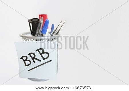 Close-up of sticky note with message on pen holder over white background