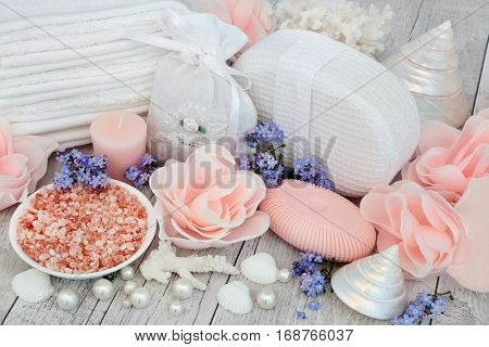 Detox spa treatment with himalayan sea salt, pink rose flower soap petals, forget me not flowers and bathroom accessories with shells and pearls.