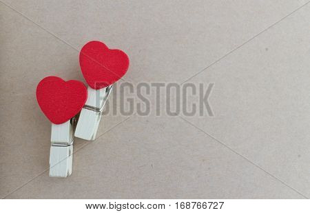 wooden clothespin with heart shape design and brown paper sheet for valentine concept