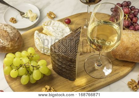 A photo of a glass of white wine with cheese, white and rye bread, red and white grapes, and walnuts, at a wine pairing. Selective focus
