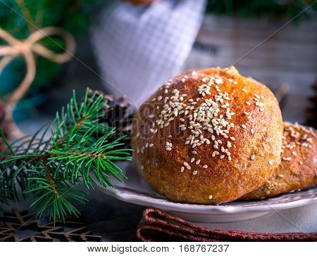 Fresh buns with sesame seeds on a plate. Whole-grain bread. The pine cones. Wooden snowflakes