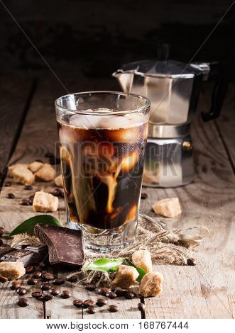 ice coffee in a tall glass with cream and coffee beans, coffee pot and a piece of chocolate on a wooden background