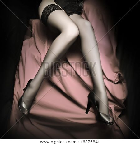 Beautiful slim legs in black nylons on a pink background. Monochrome photography - great for calendar.