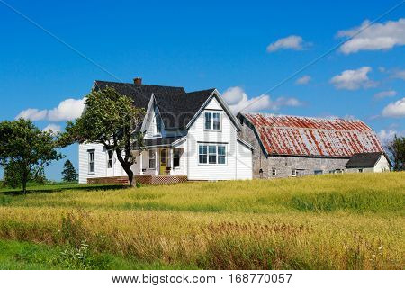 Old traditional style farmhouse with a nearby barn.