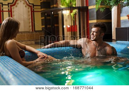 Young sexy couple in swimsuits relaxing together at jacuzzi during spa treatment at hotel
