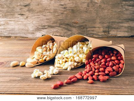 Peanuts popcorn and pistachios rolled in paper packets lying on the table. Background antique wood. Front view.Horizontal frame