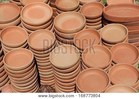 Plates of red ceramic. Background of ceramic cups