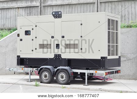 Mobile Diesel Generator on the Office Building Wall as a Background