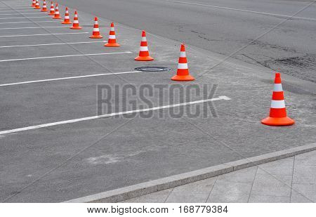 Car parking lot with white mark and traffic cone on street used warning sign on road