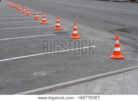 Closed car parking lot with white mark and traffic cone on street used warning sign on road