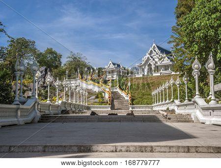Thailand Krabi Krabi town. Temple Wat Kaew Korawaram - white facade and dark blue roof. Railing stairs leading to the temple in the form of long beautiful dragons Nagi.